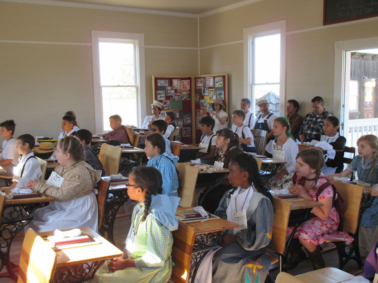 Students sitting in desks in one-room schoolhouse