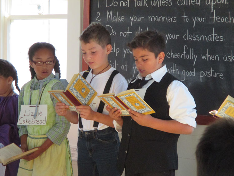 Students standing, reading from books